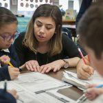 Fourth-grade teacher Bridgette McDermott, center, assists Sophia Baez with a classwork assignment at St. Elizabeth of Hungary Catholic School in Oak Cliff. McDermott is a first-year Alliance for Catholic Education teacher at the school. (JENNA TETER/The Texas Catholic)