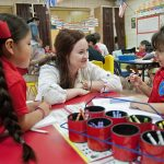 Dual language teacher Candice Baker visits with students in her classroom at Santa Clara of Assisi Catholic Academy. (JENNA TETER/The Texas Catholic)