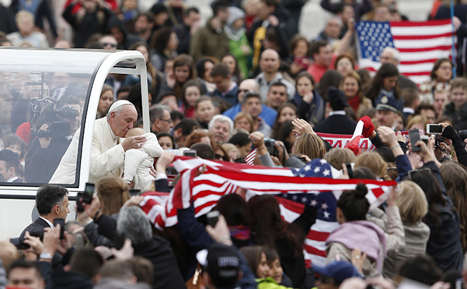 U.S. flags are seen as Pope Francis kisses a baby during his general audience in St. Peter's Square at the Vatican March 23. (CNS photo/Paul Haring)
