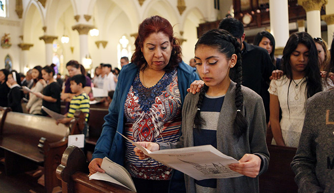 Godmother Eloina Mijares, left, places her arm on the shoulder of Catechumen candidate Melanie Munoz as Bishop Kevin J. Farrell affirms the candidates during the Rite of Election on Feb. 20 at the Cathedral Shrine of the Virgin of Guadalupe in Downtown Dallas. (BEN TORRES/Special Contributor)
