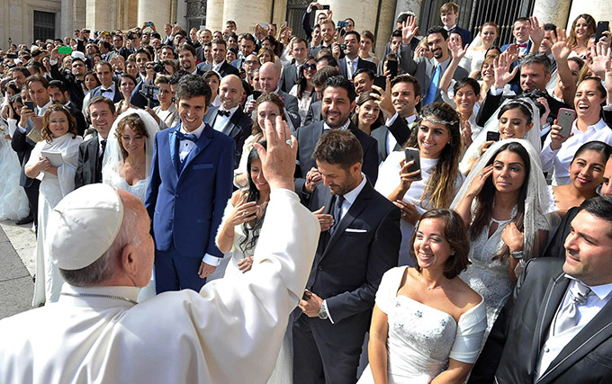 "Pope Francis greets newly married couples during his general audience in St. Peter's Square at the Vatican in this Sept. 30, 2015, file photo. Pope Francis' postsynodal apostolic exhortation on the family, ""Amoris Laetitia"" (""The Joy of Love""), was to be released April 8. The exhortation is the concluding document of the 2014 and 2015 synods of bishops on the family. (CNS photo/L'Osservatore Romano)"