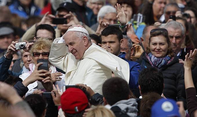 Pope Francis holds onto his zucchetto as wind blows during his general audience in St. Peter's Square at the Vatican April 27. (CNS photo/Paul Haring)