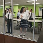Students demonstrate one of the features — the ability to write and erase on the walls and windows — in the new Technology-Enhanced Active Learning labs in the new wing of Bishop Lynch High School on April 11. (JENNA TETER/The Texas Catholic)