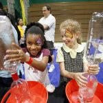 Lizzie Osborne, 9, and Savanah Wolfson, 9, shake bottles of water to create a tornado, at a JPII booth showing how tornadoes work, during STEM Day at St. Mark the Evangelist Catholic School, on Friday, April 8, 2016 in Plano. (Ben Torres/Special Contributor)
