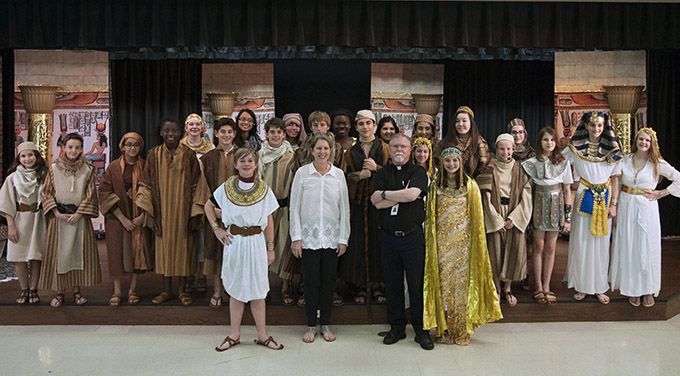 "Father Clifford Smith, pastor of St. Mark the Evangelist Catholic Church in Plano, and St. Mark the Evangelist Catholic School Musical Director Patty Corsi with the student-led cast of ""Joseph the Dreamer"" at the Plano campus on May 11. (JENNA TETER/The Texas Catholic)"