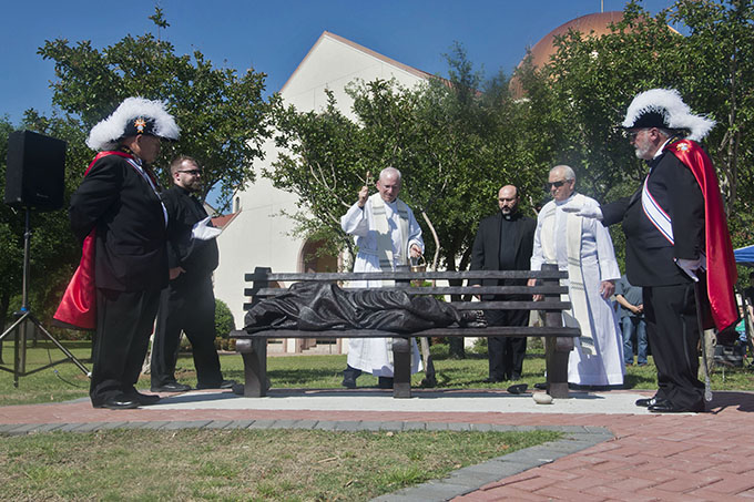 """Father Kevin Wilwert, Msgr. Henry Petter, Father Paolo Capra and Msgr. Milam Joseph dedicate and bless the new """"Homeless Jesus"""" statue at St. Ann Catholic Church in Coppell on April 30. (JENNA TETER/The Texas Catholic)"""