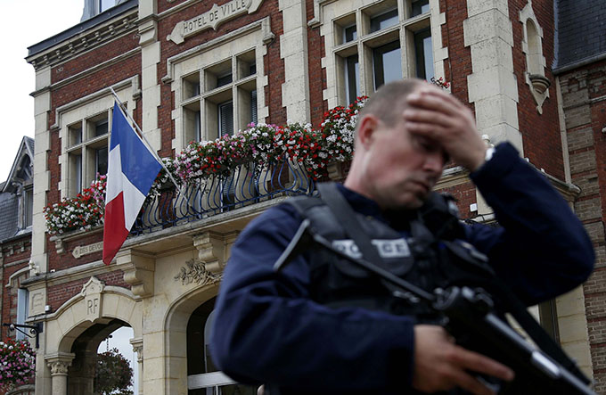 A policeman reacts as he secures a position in front of city hall after two assailants killed 84-year-old Father Jacques Hamel and took five people hostage during a weekday morning Mass at the church in Saint-Etienne-du-Rouvray, France, near Rouen July 26. (CNS photo/Pascal Rossignol/Reuters)