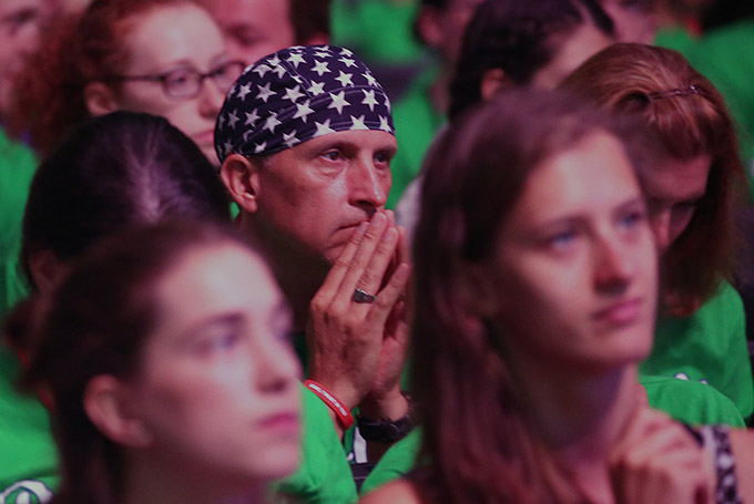 A U.S. World Youth Day pilgrim listens to Boston Cardinal Sean P. O'Malley speak July 27 at Tauron Arena in Krakow, Poland. (CNS photo/Bob Roller)