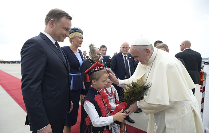Pope Francis receives a gift from a child as he is greeted by Polish President Andrzej Duda and first lady Agata Kornhauser-Duda upon his arrival at the airport in Krakow, Poland, July 27. (CNS photo/L'Osservatore Romano via EPA)