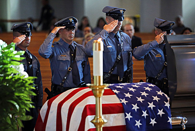 Members of the New Jersey State Police salute a casket with the body of slain Dallas police Sgt. Michael Smith during a visitation Tuesday, July 12, 2016 at Mary Immaculate Catholic Church in Farmers Branch, Texas. Smith was one of five officers killed last week when a gunman opened fire on a Black Lives Matter rally in downtown Dallas. (Pool photo/G.J. McCarthy/The Dallas Morning News)