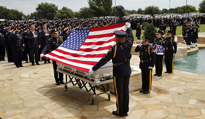 Dallas police Color Guard's Sr. Cpl. Josh Cooper (facing) and Sr. Cpl. Don Alexander prepare to fold the flag during a ceremony for officer Michael Krol outside of Prestonwood Baptist Church in Plano, Texas, Friday, July 15, 2016. Krol was gunned down in an ambush attack in downtown Dallas a week ago. Four Dallas police officers and one DART officer were killed and several survived. (Tom Fox/The Dallas Morning News, pool photo)