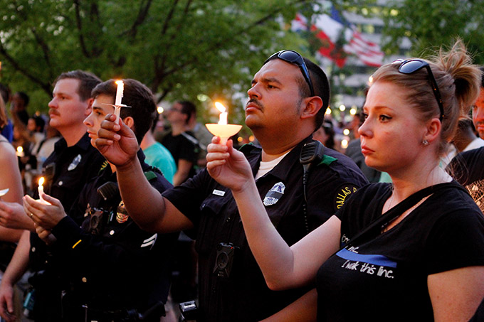 Dallas police officers hold candles during a vigil at city hall on July 11 in Dallas. Five police officers, including Officer Michael Krol, were killed on July 7 when a sniper opened fire during a protest in downtown Dallas. (KEVIN BARTRAM/Special Contributor)
