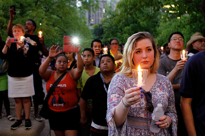 Candles are held during a vigil at city hall on July 11 in Dallas. (KEVIN BARTRAM/Special Contributor)