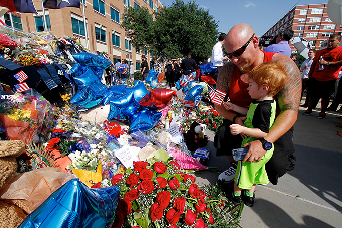 Jamie Cummings and his son T.J., 2, visit a memorial in front of the Dallas Police Department headquarters on July 11 in Dallas. Five police officers were killed on July 7 when a sniper opened fire during a protest in downtown Dallas. (KEVIN BARTRAM/Special Contributor)