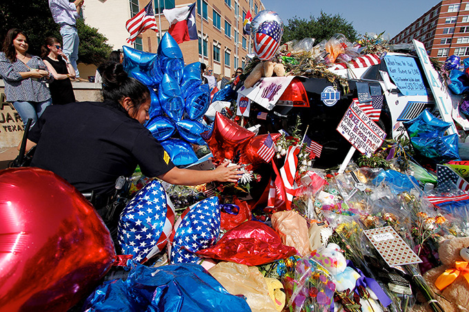 Dallas Police Department Sgt. Rocio Munoz inspects a memorial at police headquarters on July 11 in Dallas. (KEVIN BARTRAM/Special Contributor)
