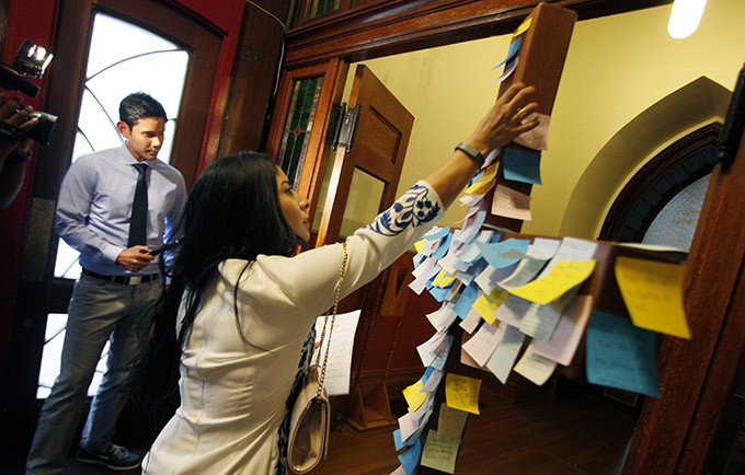 Parishioner Cassandra Hernandez leaves a message on a crucifix showing her support for the victims of the Black Lives Matter rally shooting, before the start of a Mass for Hope and Healing celebrated by Bishop Kevin J. Farrell, on July 9 at the Cathedral Shrine of the Virgin of Guadalupe in Dallas. (Ben Torres/Special Contributor)