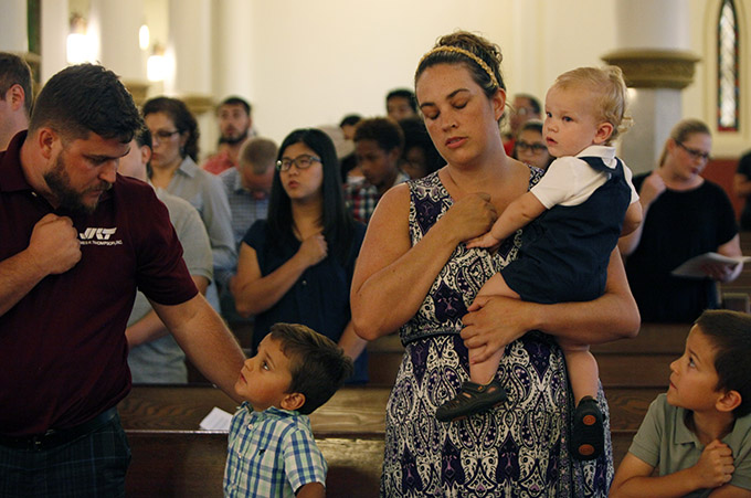 A woman and her family say a prayer at the start of Mass for Hope and Healing on July 9 at the Cathedral Shrine of the Virgin of Guadalupe in Dallas. (Ben Torres/Special Contributor)