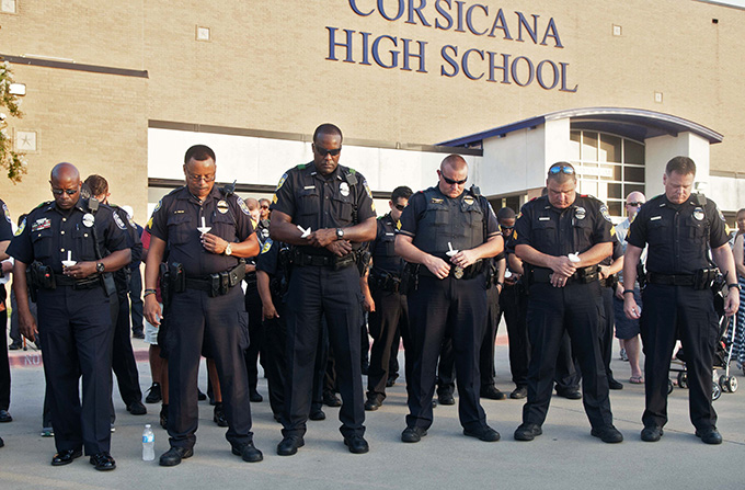 Dallas Area Rapid Transit officers bow their heads in prayer during a candlelight vigil for DART Police Officer Brent Thompson at Corsicana High School on July 10. (JENNA TETER/The Texas Catholic)
