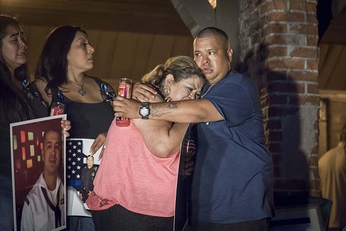 Valerie Zamarripa is hugged by her son Carlos Zamarripa after a candlelight vigil and rosary for her son, Dallas Police Officer Patrick Zamarripa, at Marine Park in Fort Worth, Texas on July 10. (RON HEFLIN/Special Contributor)
