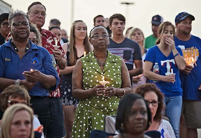 Patricia Kirkendoff of Corsicana, middle, takes part in the candlelight vigil for DART Police Officer Brent Thompson on July 10  in the parking lot at Corsicana High School. (JENNA TETER/The Texas Catholic)