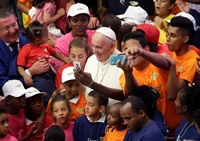 Pope Francis poses with refugees as he leads his general audience in Paul VI hall at the Vatican Aug. 3. (CNS photo/Max Rossi, Reuters)