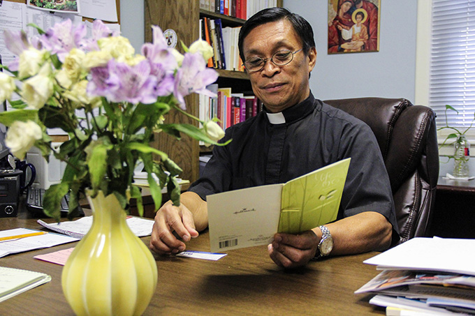 Father Albert Becher, pastor of Holy Family of Nazareth Catholic Church in Irving, reads over a card given to the parish from the Islamic Center and School of Irving.