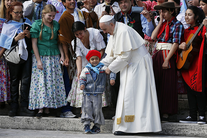 Pope Francis positions a boy for a photo as he meets an Argentine group during his general audience in St. Peter's Square at the Vatican Oct. 19. (CNS photo/Paul Haring)