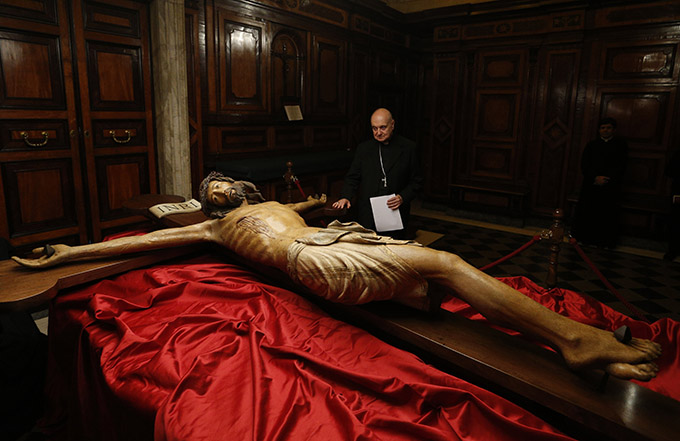 Cardinal Angelo Comastri, archpriest of St. Peter's Basilica, looks at a wooden crucifix from the 14th century during a media opportunity to showcase its restoration in St. Peter's Basilica at the Vatican Oct. 28. The crucifix is one of the few items that was present in the original St. Peter's Basilica. The restoration was funded by the Knights of Columbus. (CNS photo/Paul Haring)