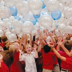 Students are surrounded by falling balloons as they gather to celebrate the announcement of Prince of Peace Catholic School in Plano as a 2016 National Blue Ribbon School by the U.S. Department of Education. (JENNA TETER/The Texas Catholic)