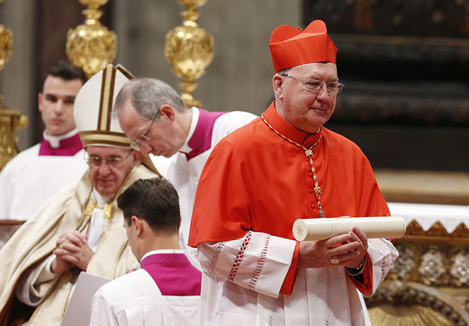 New Cardinal Kevin J. Farrell, prefect of the new Vatican office for laity, family and life, carries his scroll after being made a cardinal by Pope Francis during a consistory in St. Peter's Basilica at the Vatican Nov. 19. The pope created 17 new cardinals.(CNS photo/Paul Haring)