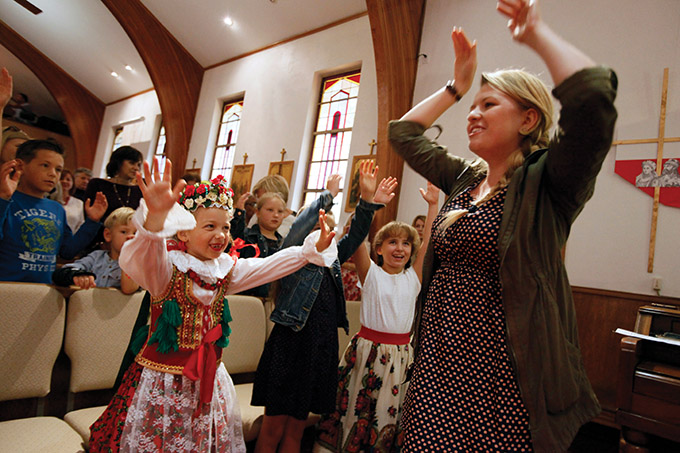 Sara Smolinski, left, with a group of young girls, follows choir director Basia Gala as they sing a Polish-Catholic song during a special Mass celebrating 30 years of Polish culture at St. Peter the Apostle Catholic Church on Oct. 23 in Dallas. (Ben Torres/Special Contributor)