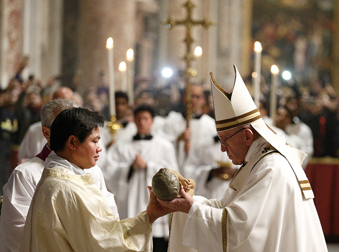 Pope Francis presents a figurine of the baby Jesus to an altar server at the conclusion of Christmas Eve Mass in Peter's Basilica at the Vatican Dec. 24. (CNS photo/Paul Haring)