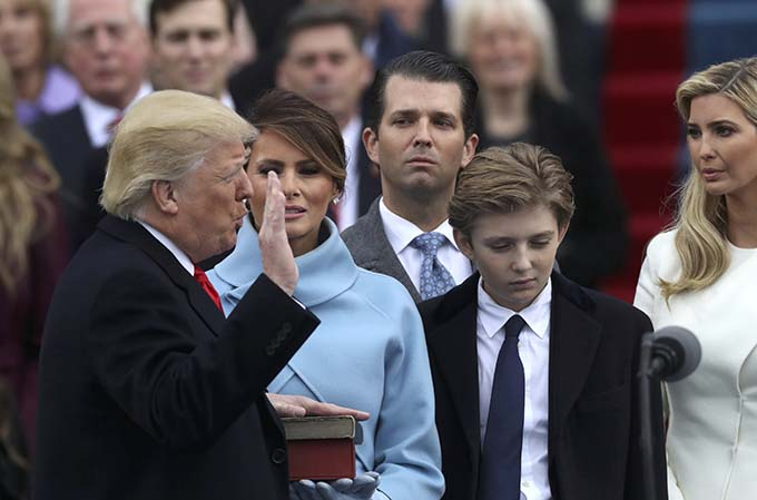 U.S. President Donald Trump places his hand on the Bible as he takes the oath of office administered by U.S. Chief Justice John Roberts Jan. 20. At Trump's side are his wife, Melania, and children Barron, Donald and Ivanka during his swearing-in as the country's 45th president at the U.S. Capitol in Washington. (CNS photo/Carlos Barria, Reuters)