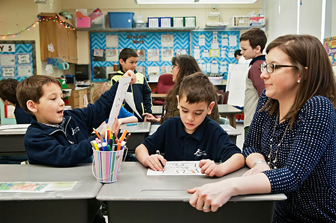 Principal Nicole Miller visits with students during an activity in their classroom at Holy Name Catholic School in Ketchikan, Alaska. (JENNA TETER/The Texas Catholic)