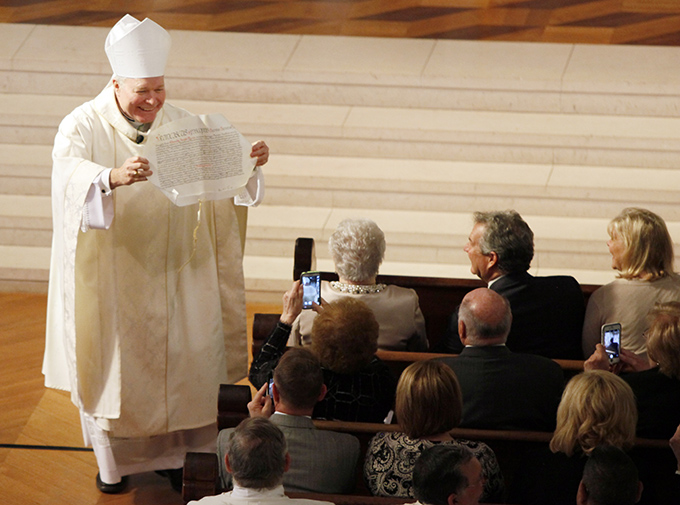 Bishop Edward J. Burns shows his mother, Geraldine Burns, the papal bull, a decree from Pope Francis declaring him the Bishop of Dallas, during his installation Mass on Feb. 9 at the Cathedral Shrine of the Virgin of Guadalupe. (BEN TORRES/Special Contributor)