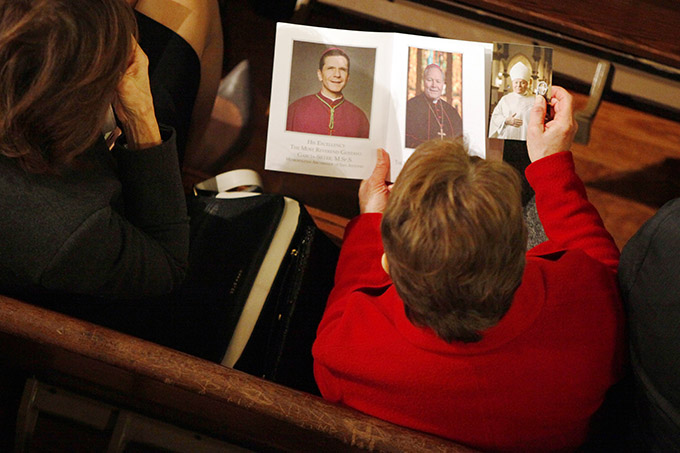 A parishioner looks at the Mass program before the start of the installation Mass for Bishop Edward J. Burns, as the eighth bishop of the Diocese of Dallas on Feb. 9 at the Cathedral Shrine of the Virgin of Guadalupe in downtown Dallas. (BEN TORRES/Special Contributor)