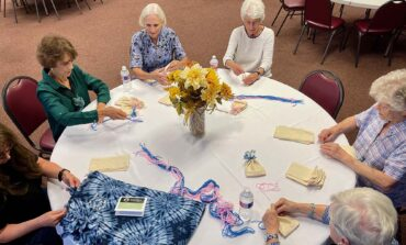 Common thread binds together group crafting baby caps